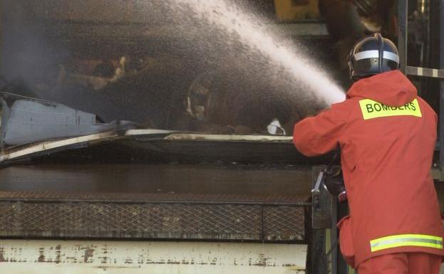 Imagen de archivo de un bomberos sofocando un incendio industrial./Damián Torres