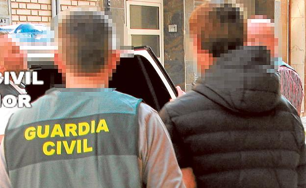 Un agente de la Guardia Civil conduce al detenido por acoso sexual.