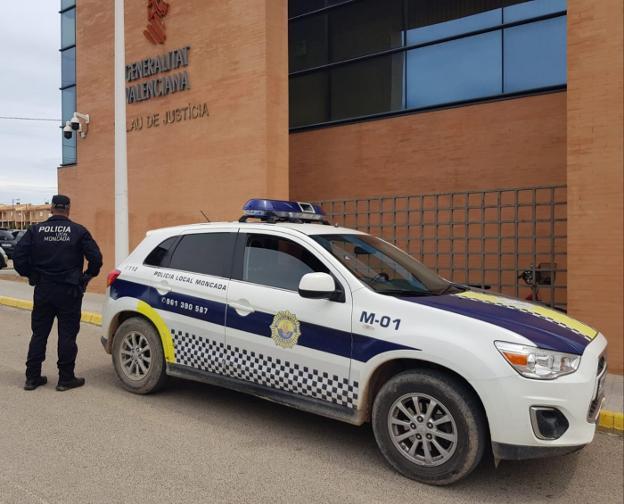 Un agente, junto a una patrulla de la Policía Local, en la puerta de los juzgados de Moncada. / lp