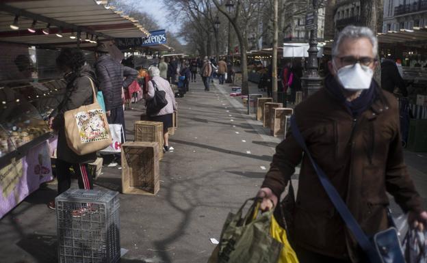 Un comprador se protege con una mascarilla en un mercado al aire libre en París el pasado domingo
