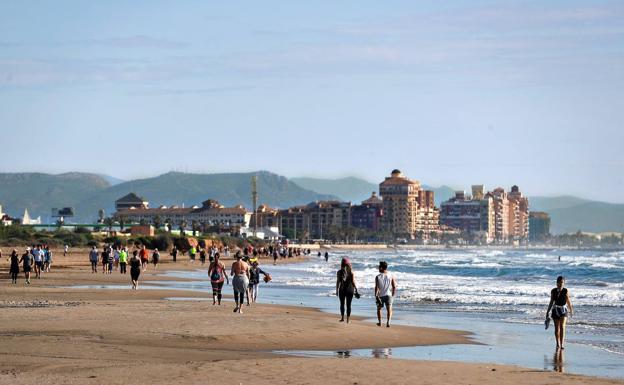 Ciudadanos pasean por la playa de Alboraya, este domingo./MANUEL BRUQUE/EFE