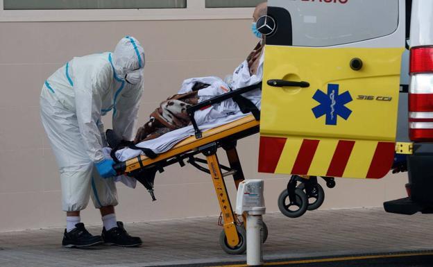 Un trabajador sanitario traslada a un paciente al Hospital Clínico de Valencia./EFE